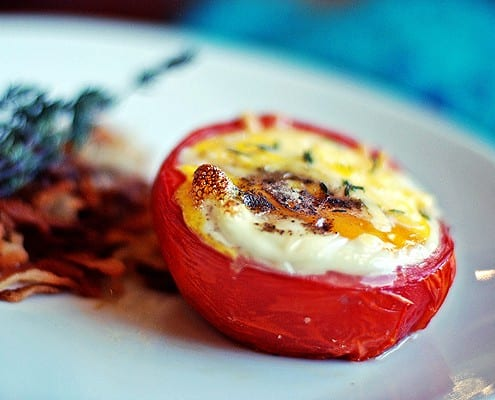 Three-cheese baked egg in a tomato cup