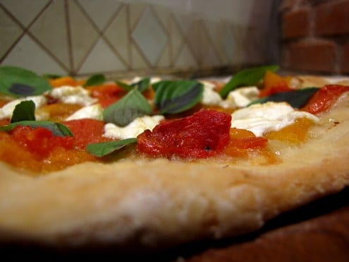 The intense heat of the wood-burning oven transforms the persimmon into a jelly, fusing it to the pizza crust.