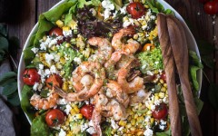 A large bowl of Grilled Shrimp and Corn Salad is displayed on a dark wood backdrop and photographed from the top view.
