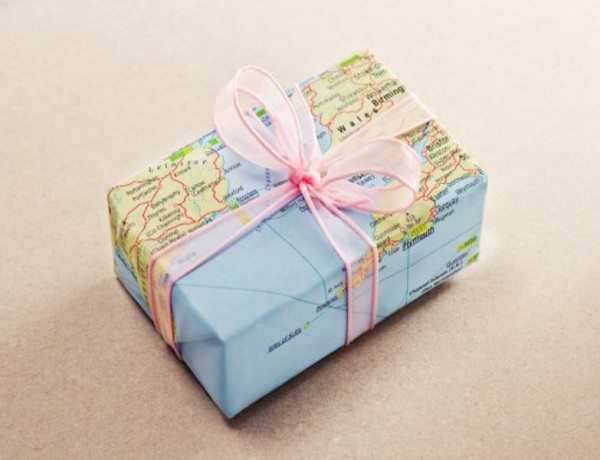 A bon voyage gift for travelers wrapped with map paper and pink bow. (Thinkstock photo)